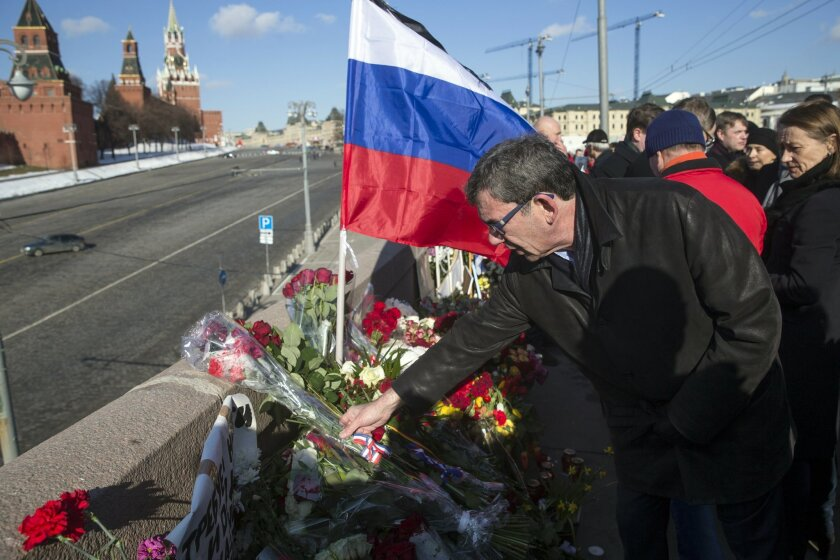 French Ambassador to Russia Jean Maurice Ripert lays flowers at the place where Russian opposition leader Boris Nemtsov was gunned down, to mark the anniversary of his killing in Moscow, with the Kremlin wall at left, Russia, Sunday, Feb. 28, 2016. More than 30,000 people marched across downtown Moscow on Saturday in memory of the slain Russian opposition leader Boris Nemtsov to mark the anniversary of his killing. (AP Photo/Pavel Golovkin)