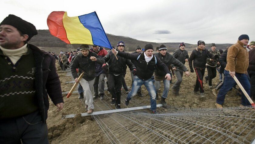 Anti-shale gas exploration protesters bring down a fence in Pungesti, north eastern Romania, Saturday, Dec. 7, 2013. Hundreds of villagers destroyed the fences around a plot of land owned by US energy company Chevron, during protests meant to stop shale gas exploration in the area. (AP Photo/Mircea