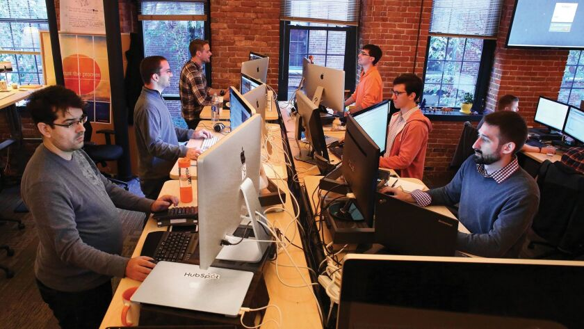 Office workers use standing desks in Cambridge, Mass. A new study tallies the health benefits of standing for six hours a day instead of sitting.