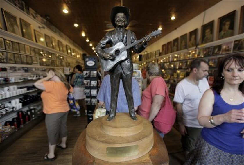 A statue of Erenest Tubbs greets shoppers as Ernest Tubbs Record Shop, Wednesday, June 9, 2010, in Nashville, Tenn. As the CMA Music Festival kicks off, business, and entertainers are hopeful that the local economy with get a big boost from tens of thousands of country music fans coming to town as the Nashville area continues to recover from last months devastating floods. (AP Photo/M. Spencer Green)