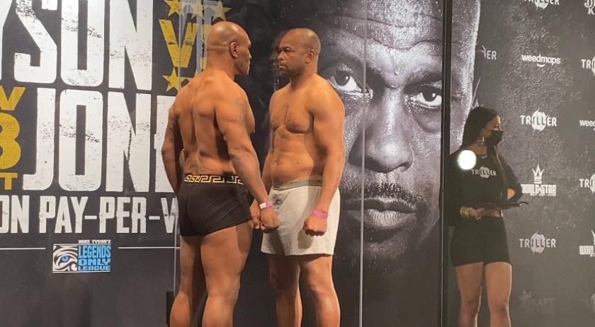 Mike Tyson, left, and Roy Jones Jr. have a staredown while separated by plexiglass after their weigh-in on Friday.