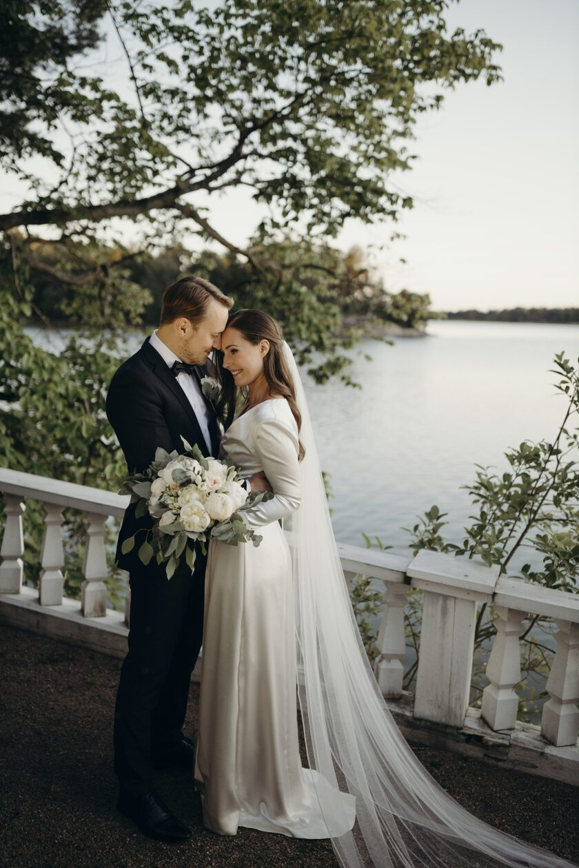 In this handout photo provided by the Finnish Prime Minister's Office on Sunday, Aug. 2, 2020, Finnish Prime Minister Sanna Marin and her new husband Markus Raikkonen pose for a photo after their wedding, at the PM's official residence Kesaranta in Helsinki. Finland's Prime Minister Sanna Marin announced Sunday that she has married her long-time partner, nine months after becoming the head of government. (Minttu Saarni/Finnish Prime Minister's Office via AP)