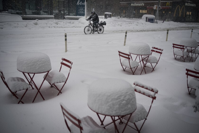 A man delivers food on his electric bicycle as he rides past snow-covered dining tables in midtown during a snowstorm, Monday, Feb. 1, 2021, in New York. (AP Photo/Wong Maye-E)