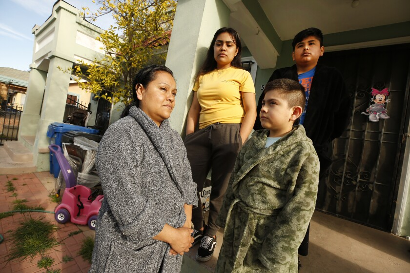 Raquel Lezama, left, and her three children, in front of their Los Angeles home.