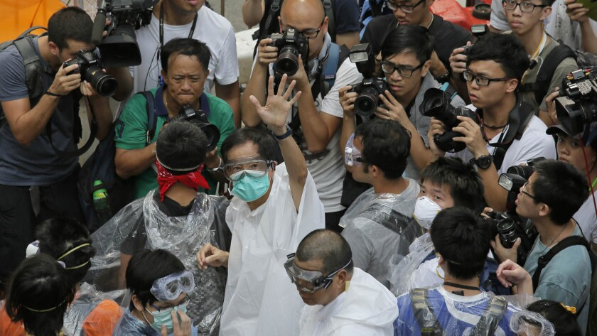 Activist Martin Lee, center, wearing goggles and a mask, waves to reporters outside government headquarters in Hong Kong.