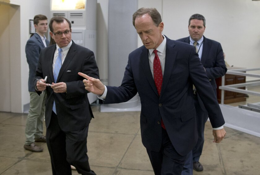 Sen. Patrick Toomey, R-Pa., center, walks towards the Senate on Capitol Hill, Monday, June 20, 2016 in Washington. A divided Senate hurtled Monday toward an election-year stalemate over curbing guns, eight days after Orlando's mass shooting horror intensified pressure on lawmakers to act but left t