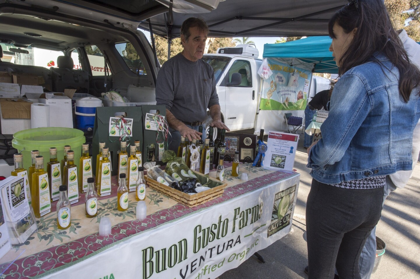 Mark Mooring of Buon Gusto Farms sells olive oil pressed from olives he grows in Ventura.