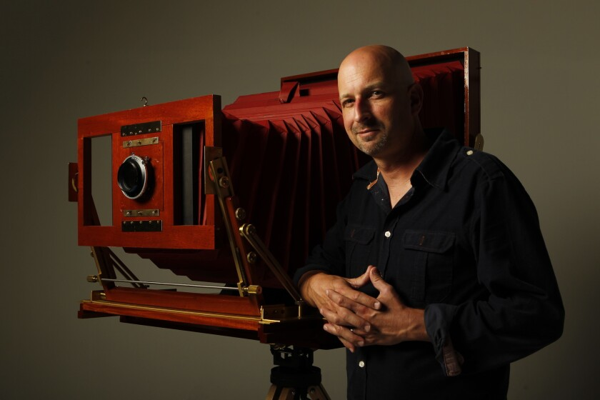 """Tim Mantoani in 2012 with the camera he used for his """"Behind Photographs"""" project."""
