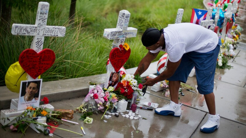 David Collins leaves flowers at a cross honoring Shane Evan Tomlinson. A retired carpenter from Illinois built and delivered crosses for each of the 49 victims of the Pulse nightclub massacre in Orlando, Fla.