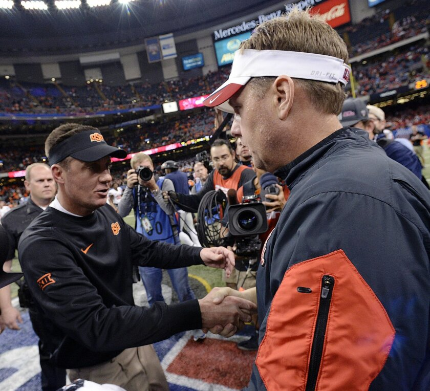 Mississippi head coach Hugh Freeze, right, greets Oklahoma State head coach Mike Gundy after the Sugar Bowl college football game in New Orleans, Friday, Jan. 1, 2016. Mississippi won 48-20. (AP Photo/Bill Feig)