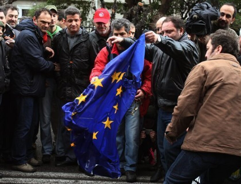 Demonstrators try to burn a European Union's flag during a protest outside EU offices in Athens on Wednesday, Feb. 10, 2010. About 7,000 people took part in two separate, peaceful marches in Athens, against the center-left government's austerity plan to ease Greece out of a major debt crisis. (AP Photo/Thanassis Stavrakis)