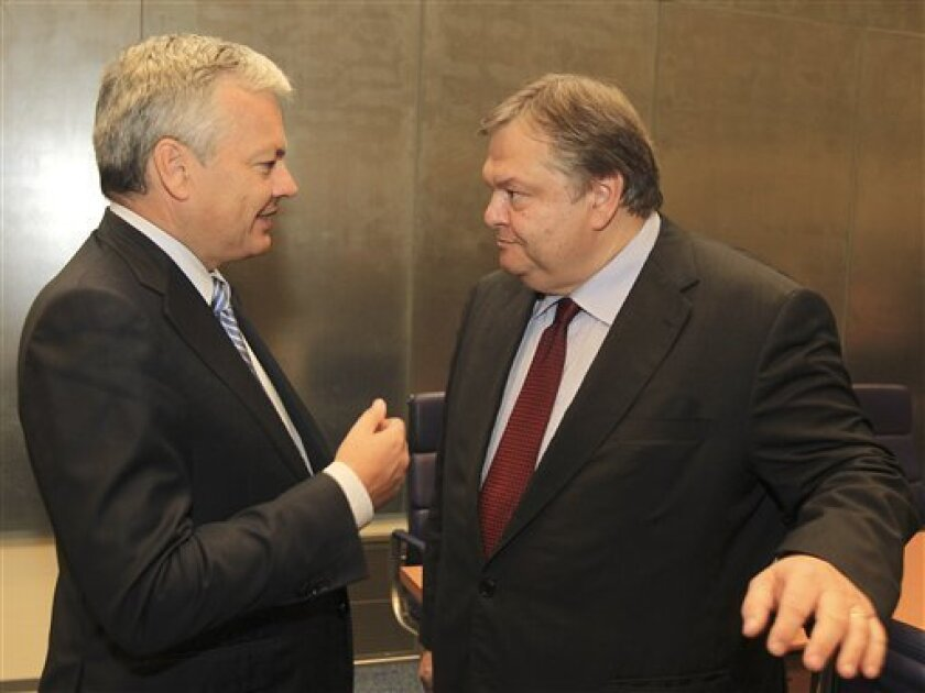 Belgian Finance Minister Didier Reynders, left, talks with Greek Finance Minister Evangelos Venizelos, during the Eurogroup ministers meeting in Luxembourg, Monday Oct. 3, 2011. The eurozone's financial chiefs faced tough decisions over how to deal with Greece's debt crisis on Monday after Athens' admission that its deficit will be higher than promised sent markets tumbling. (AP Photo/Yves Logghe)