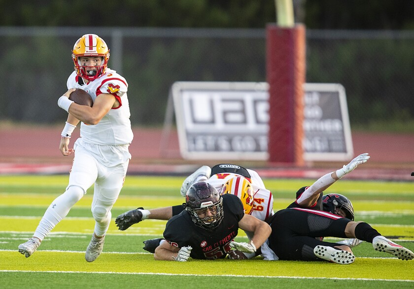 Mission Viejo quarterback Kadin Semonza runs past San Clemente High players in April.