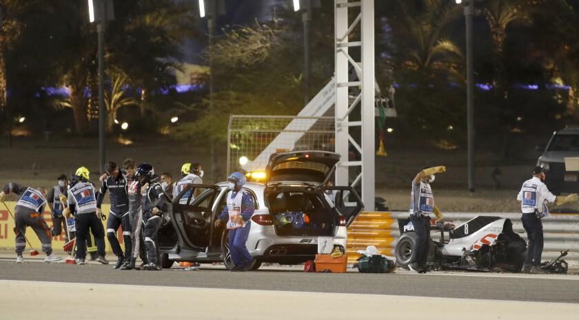 El piloto Romain Grosjean del equipo Haas recibe auxilio tras estrellar su monoplaza en el Gran Premio de Bahréin