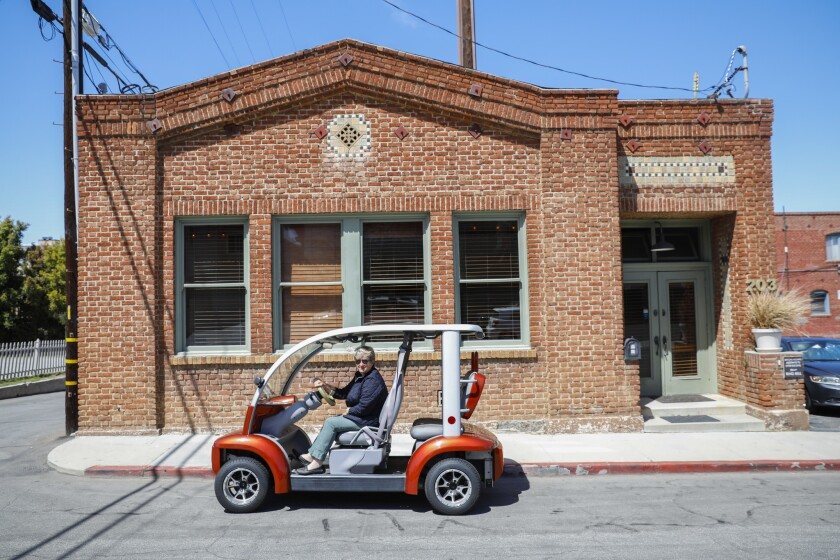 Julie Stolnack, a fourth-generation resident who uses an electric cart to get around El Segundo, is shown outside a century-old building that was formerly the police station.