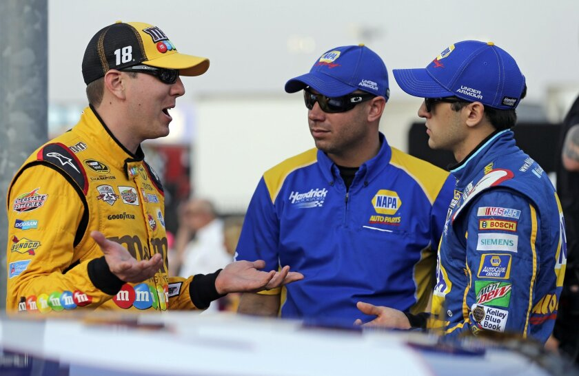 Kyle Busch, left, talks with Chase Elliott, right, before qualifying for Sunday's NASCAR Sprint Cup series auto race at Charlotte Motor Speedway in Concord, N.C., Thursday, May 26, 2016. (AP Photo/Chuck Burton)