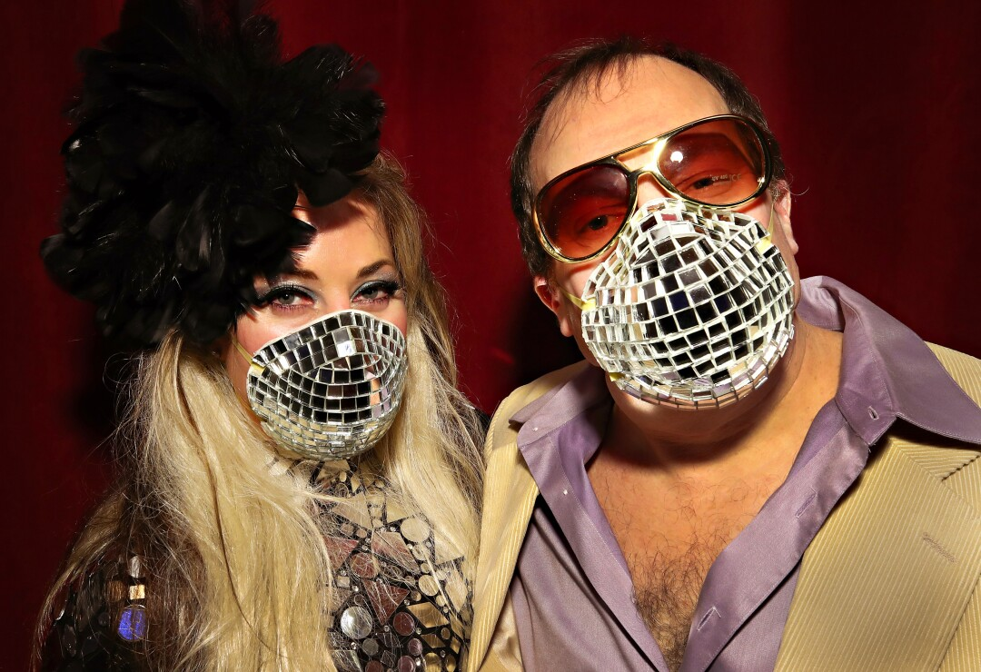 """UNITED STATES: Allison Eden and Gary Goldenstein wear disco-ball-inspired masks during the opening of the """"Studio 54: Night Magic"""" exhibit at the Brooklyn Museum in New York."""