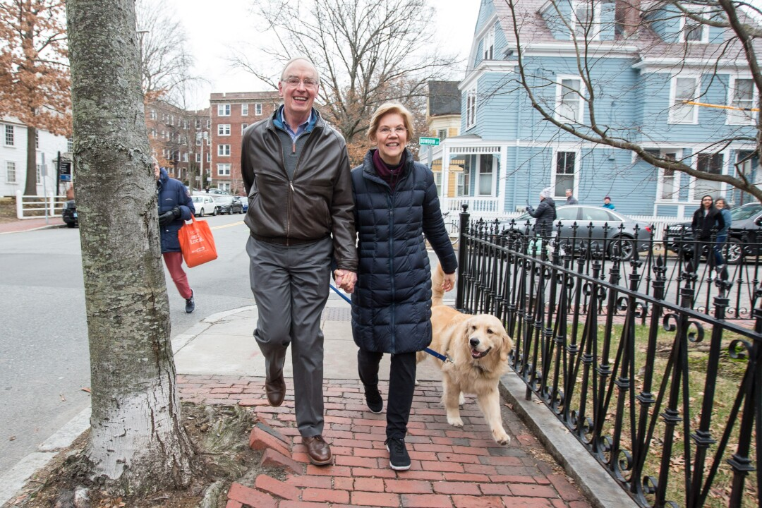 Sen. Elizabeth Warren, her husband, Bruce Mann, and their dog, Bailey, walk home after Warren announced the exploratory committee for her presidential run in Cambridge in 2018.
