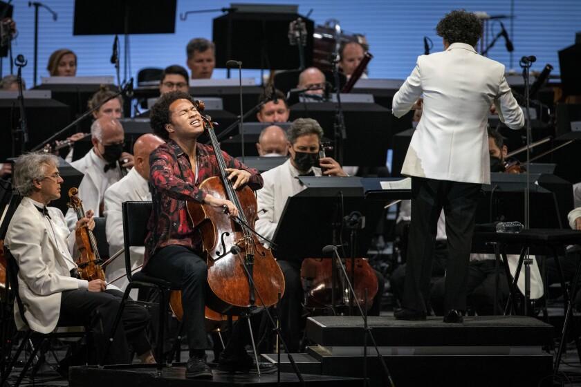 Sheku Kanneh-Mason plays his cello as Gustavo Dudamel conducts musicians.