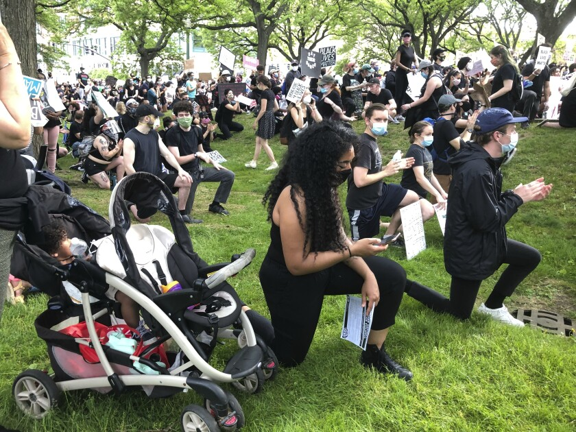 Anjel Newmann, 32, kneels while scanning her phone during a peaceful rally in Providence, R.I. on Friday, June 5. Newmann said she's mostly using Instagram and Facebook to organize protests while people younger than her are using Snapchat. (AP Photo/Matt O'Brien)