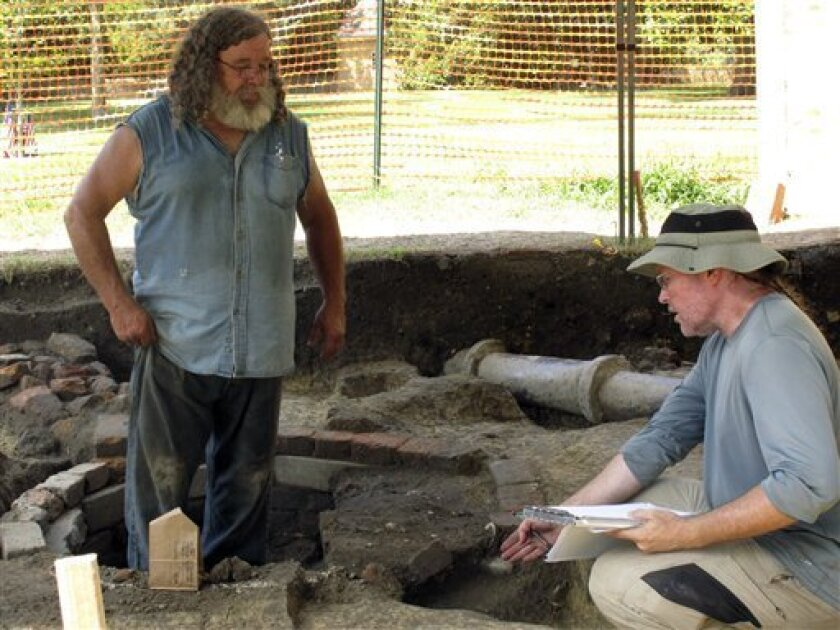 Archaeologists Kevin Goodrich, right, and Jack Aube, left, of the William and Mary Center for Archaeological Research, examine a well dug on the campus of the College of William and Mary by Union troops during the Civil War in this Friday, July 27, 2012 photo in Williamsburg, Va. Archaeologists say they have found the remnants of a Civil War encampment used by Union troops who controlled the campus from 1862 to 1865. (AP Photo/Brock Vergakis)
