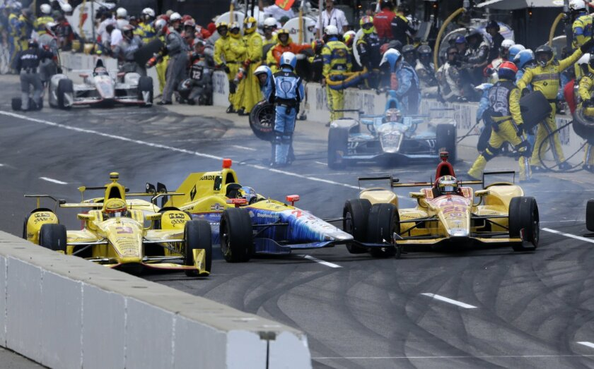 The cars driven by Helio Castroneves, of Brazil, left, Townsend Bell, center, and Ryan Hunter-Reay collide as they exit the pit area during the 100th running of the Indianapolis 500 auto race at Indianapolis Motor Speedway in Indianapolis, Sunday, May 29, 2016. (AP Photo/R Brent Smith)
