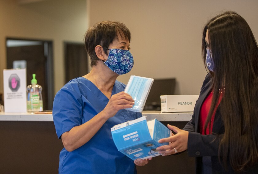 Dr. Quynh Kieu, left, founder and president of Project Vietnam Foundation, receives masks from Vivian Cao.