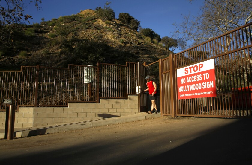 A runner walks out of a gate that leads to a hiking path that offers views of the Hollywood sign. The path reopened Monday after an electric gate was installed that will limit car traffic going up the trail, but will give hikers access during the park's hours.
