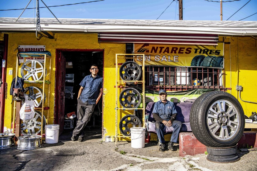 "LOS ANGELES, CA - MARCH 26: Luis Moreno, left, and Author Bernal, both employees at Flaco's Tires on Thursday, March 26, 2020 in Los Angeles, CA. Moreno, who lives with his girlfriend and their 5 year old son, agreed to a pay reduction as business has been hit hard by the coronavirus pandemic. ""We normally do at least fifteen cars a day"" said Moreno, ""Now, it's maybe four"". (Mariah Tauger / Los Angeles Times)"