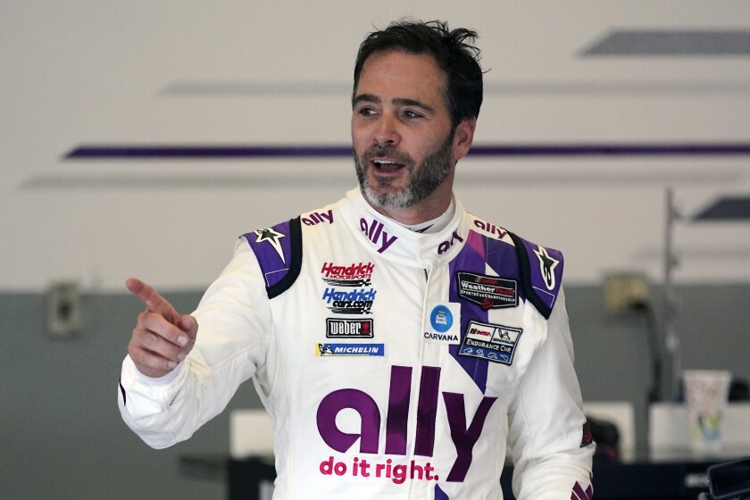 Jimmie Johnson interacts with crew members during a practice session for the Rolex 24, an endurance race at Daytona.