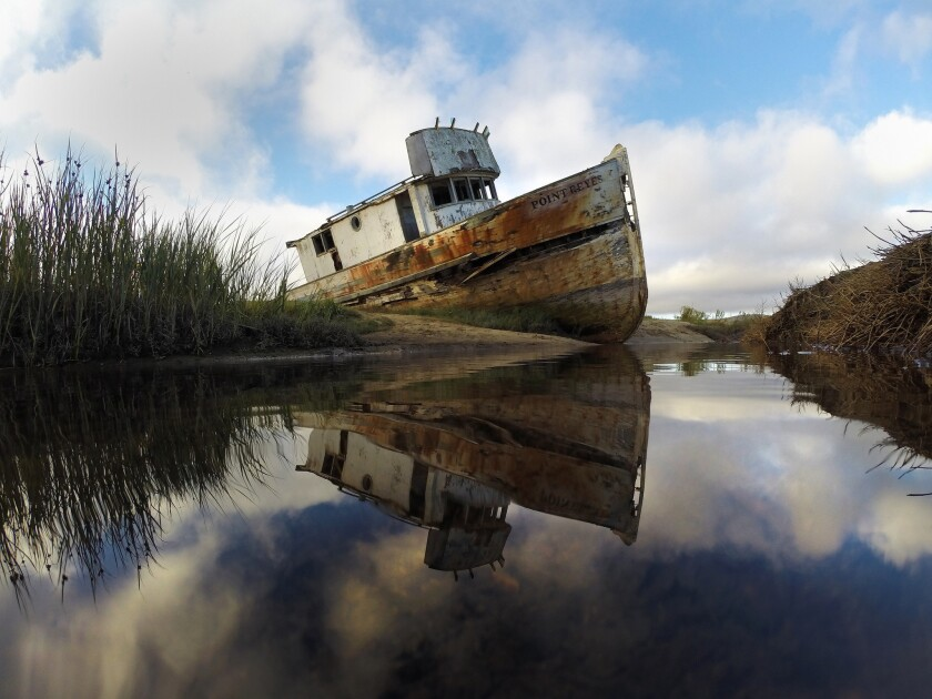 A marooned fishing boat is reflected in low tide pools along Tomales Bay at Point Reyes National Seashore.