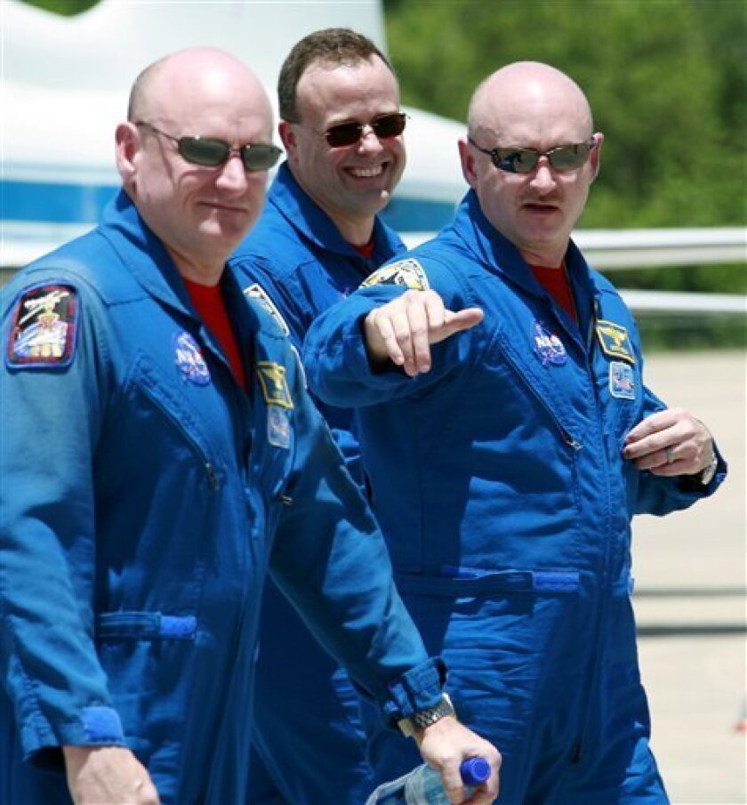 FILE - In this May 28, 2008 file photo, Space shuttle Discovery commander Mark Kelly, husband of Rep. Gabrielle Giffords, right, gestures as he walks with his twin brother astronaut Scott Kelly, left, and mission specialist Ron Garan, after arrival at Kennedy Space Center in Cape Canaveral, Fla. The shocking gundown of Rep. Gabrielle Giffords on Saturday, Jan. 8, 2011 has left NASA reeling: Her astronaut husband was due to rocket away in just three months as perhaps the last space shuttle commander, and her brother-in-law is currently on the International Space Station. (AP Photo/Terry Renna, File)