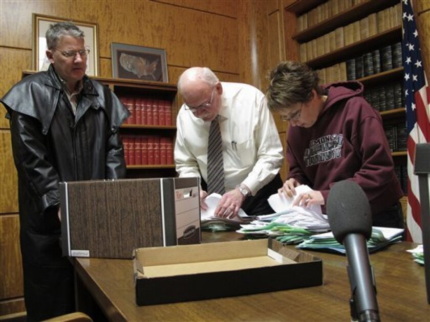 North Dakota Secretary of State Al Jaeger, center, and Jaeger's elections director, Lee Ann Oliver, right, dig through stacks of referedum petitions on Tuesday, Feb. 7, 2012, in the secretary of state's office in the North Dakota Capitol in Bismarck, N.D., as Reed Soderstrom, left, a Minot attorney, looks on. Soderstrom is chairman of a referendum campaign to require the University of North Dakota to use its Fighting Sioux athletics nickname and a logo that features the profile of an American Indian warrior. The university wants to retire the nickname and logo, which the NCAA considers offensive. (AP Photo/Dale Wetzel)