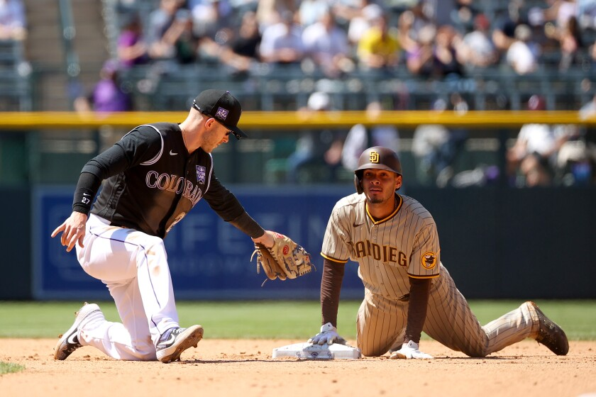 The Padres' Tucupita Marcano slides safely into second base ahead of a tag by Rockies shortstop Trevor Story on Wednesday.
