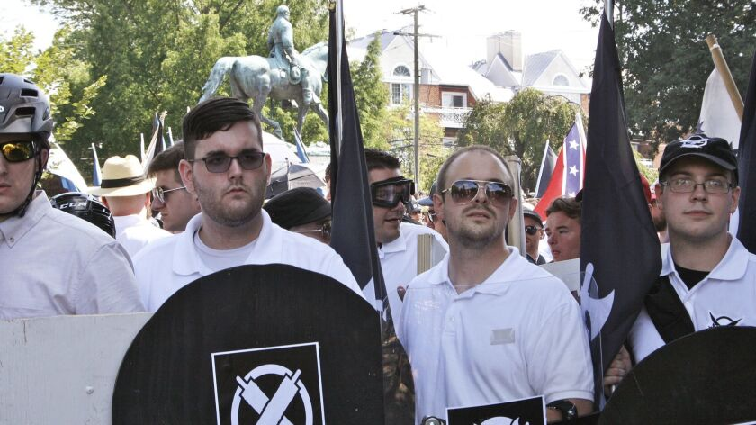 James Alex Fields Jr., second from left, with a shield bearing the logo of the white supremacist group Vanguard America during a rally in Charlottesville, Va., on Aug. 12, 2017.