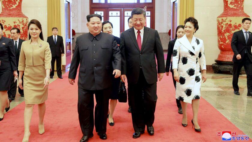 In this March 26, 2018, photo, North Korean leader Kim Jong Un, center left, his wife Ri Sol Ju, lef