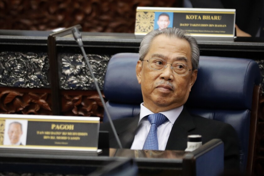 FILE - In this July 13, 2020, file photo, Malaysian Prime Minister Muhyiddin Yassin attends a Parliament session at lower house in Kuala Lumpur, Malaysia. A second Malaysian Cabinet minister resigned Friday, Aug. 6, 2021, dealing another blow to embattled Muhyiddin, who insisted he has majority support in Parliament despite the pullout of some governing alliance members. (AP Photo/Vincent Thian, File)