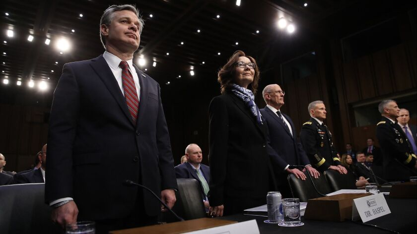 FBI Director Christopher A. Wray, left, CIA Director Gina Haspel and Director of National Intelligence Dan Coats, followed by other intelligence agency officials, await the start of a Senate Intelligence Committee hearing on Jan. 29, 2019.