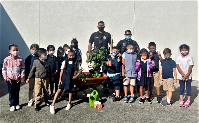 CMPD school resource officers Anthony Melendez, center, and Eloisa Peralta with Rea Elementary School students.