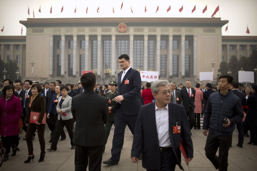 In this March 14, 2018, file photo, former NBA basketball player Yao Ming (center) leaves after a plenary session of the CPPCC at the Great Hall of the People in Beijing. Yao is now president of the Chinese Basketball Association, which announced over the weekend it is suspending its ties with the Houston Rockets in retaliation for General Manager Daryl Morey's tweet that showed support for Hong Kong anti-government protesters.