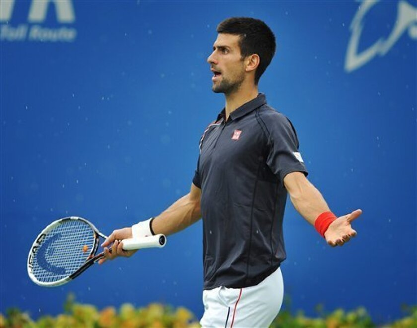 Novak Djokovic of Serbia reacts to a rain delay during his match against Sam Querrey of the United States at the Rogers Cup men's tennis tournament in Toronto, Friday, Aug. 10, 2012. (AP Photo/The Canadian Press, Aaron Vincent Elkaim)