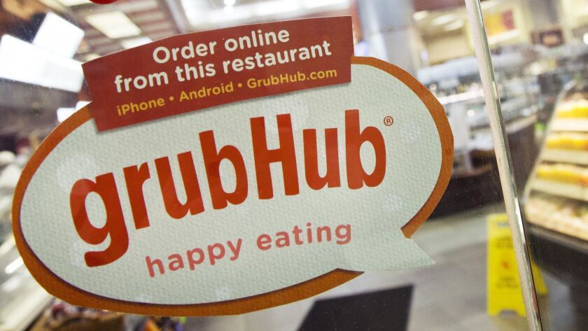 A sign for Grubhub is displayed April 4, 2014, on the door to a New York restaurant. Grubhub has expanded its reach though a partnership with Taco Bell parent Yum Brands.