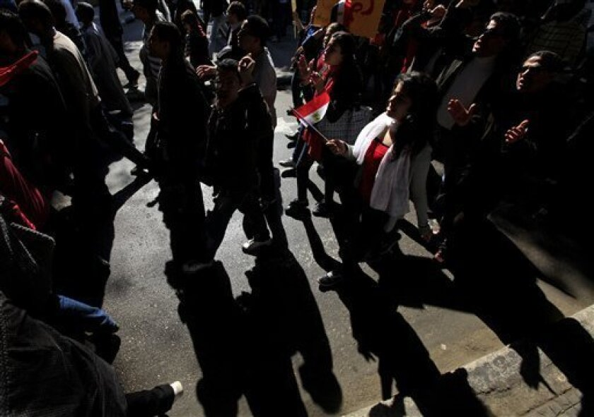 Anti-government protesters march in Cairo street, Egypt, Friday, Feb. 11, 2011. Egypt's military threw its weight Friday behind President Hosni Mubarak's plan to stay in office through September elections while protesters fanned out to the presidential palace in Cairo and other key symbols of the a