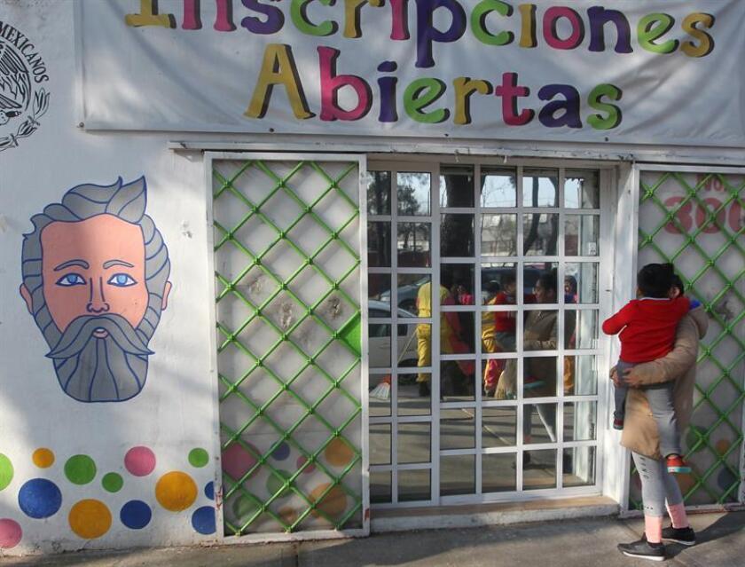 Una mujer llega con su hijo a la entrada de una guardería en Ciudad de México (México). EFE/Archivo