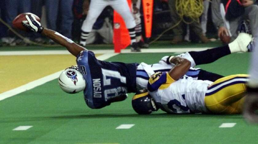 Tennessee Titans wide receiver Kevin Dyson tries but fails to get the ball into the end zone as he is tackled by the St. Louis Rams' Mike Jones on the final play of Super Bowl XXXIV.