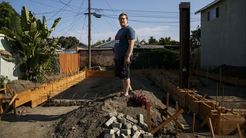 John Gregorchuk standing in the midst of an accessory dwelling unit construction that has been stalled in his backyard, in Los Angeles in August 2016.