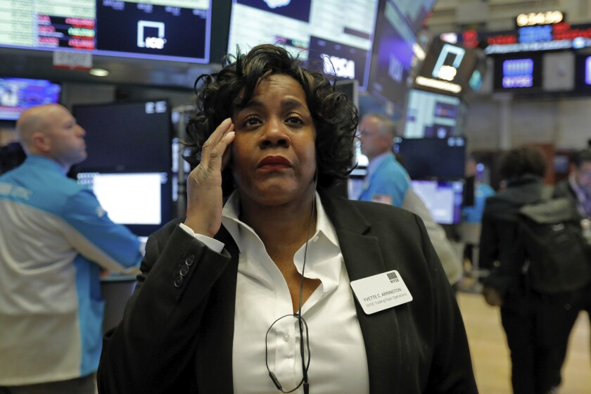 Yvette Arrington, with the New York Stock Exchange Trading Floor Operations, works on the floor of the NYSE, Monday, March 9, 2020. Stocks went into a steep slide Monday on Wall Street as coronavirus fears and a crash in oil prices spread alarm through the market, triggering the first automatic trading halt in over two decades. (AP Photo/Richard Drew)