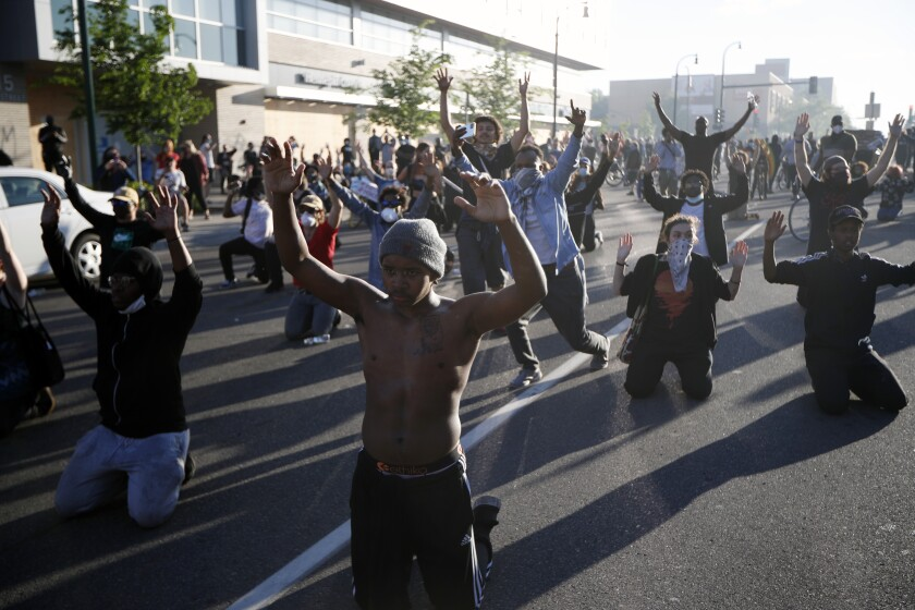 Demonstrators gather in the street with their hands raised Friday, May 29, 2020, in Minneapolis.