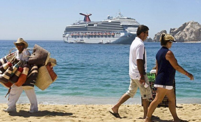 A beach vendor, left, looks for a sale as tourists walk on Medano Beach as a cruise ship is anchored offshore in Los Cabos, Baja California, Mexico.