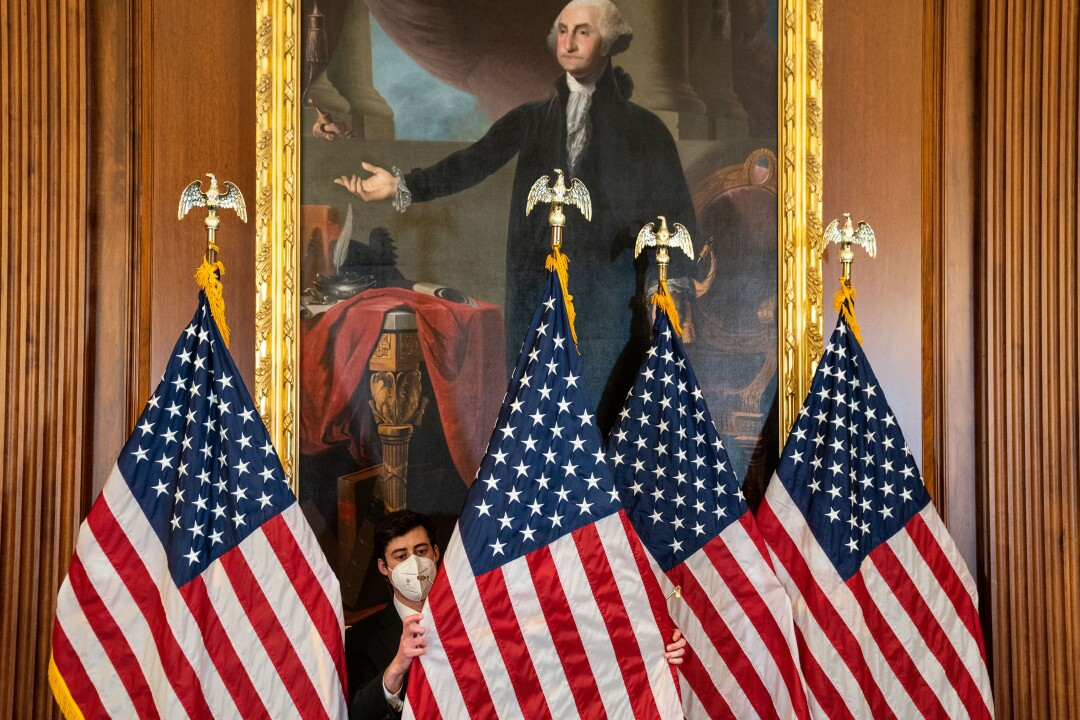 A congressional staffer adjusts several flags